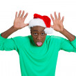 Closeup portrait of mean young man in red santa claus hat placing thumbs on head sticking tongue out at camera gesture — Stock Photo #37399477