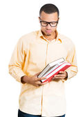 Closeup of a young handsome nerdy man, wearing big glasses, holding books, anxious in anticipation of finals, exam test — Foto Stock