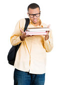 Closeup of a young handsome man, wearing big glasses, holding books, anxious in anticipation of finals, exam test — 图库照片