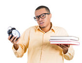 Closeup of young handsome man, wearing big glasses, holding books, clock, anxious in anticipation of finals test, running out of time — Foto de Stock