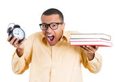 Closeup of young handsome man, wearing big glasses, holding books, clock, anxious in anticipation of finals test, running out of time — Stockfoto