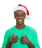 Closeup portrait of young handsome happy, smiling excited man in red santa hat giving two thumbs up sign with fingers — Stock Photo