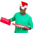 Closeup portrait of young man in red santa claus hat opening gift, very upset at what he received — Stock Photo #37401203