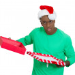 Closeup portrait of young man in red santa claus hat opening gift, very upset at what he received — Stock Photo #37401207