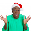 Closeup portrait of shocked, surprised, astonished man, worker wearing red santa claus hat, hands in air, mouth eyes wide open — Stock Photo #37401219