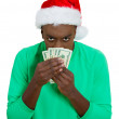 Closeup portrait of grumpy greedy miserly young man wearing red santa claus hat holding and protecting his money dollars in hand — Stock Photo