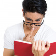 Closeup portrait of a nerdy guy, wearing black glasses, reading a book, immersed in a story — Stock Photo #37402791