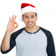 Closeup portrait of young handsome smiling, winter man wearing red santa claus hat, showing an OK sign gesture — Stock Photo