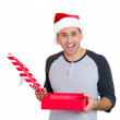 Closeup portrait of a young handsome excited man wearing red santa claus hat, opening gift box and super happy at what he gets — Zdjęcie stockowe