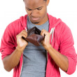 Closeup portrait of stressed, upset, sad, unhappy young man standing with, looking into empty wallet — Stock Photo #37404973