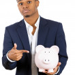 Stock Photo: Closeup portrait of rich young successful mintroducing his friend, piggy bank