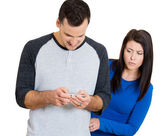 Closeup portrait of sneaky jealous possessive girlfriend watching boyfriend happily texting someone else — Stock Photo