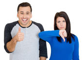 Closeup portrait of young couple, man, woman. One being excited happy smiling, showing thumbs up, other serious, concerned, unhappy showing thumbs down — Stock Photo