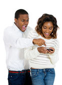 Closeup portrait of angry jealous possessive boyfriend pointing at girlfriend happily texting someone else — Stock Photo
