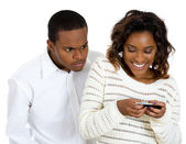 Closeup portrait of angry jealous possessive boyfriend watching girlfriend happily texting someone else — Stock Photo