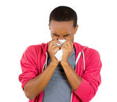 Closeup portrait of young man in red hoodie with allergy or cold, blowing his nose with a tissue, looking miserable unwell very sick — Stock Photo