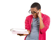 Closeup of a young handsome man, wearing big glasses, holding books, anxious in anticipation of finals, exam test — Foto de Stock