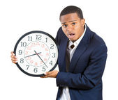 A closeup portrait of a business man, executive, leader holding a clock, very determined, pressured by lack of time, running out of time, late for the meeting — Foto Stock