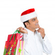 Closeup portrait of happy young handsome man in red santa claus hat holding shopping bag over shoulder looking upwards — Stock Photo