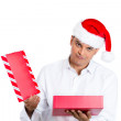 Stock Photo: Closeup portrait of young man in red santa claus hat opening gift and very upset at what he received
