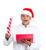 Closeup portrait of handsome young man wearing red santa claus hat, shirt, opening gift and happy at what he gets — Stock Photo