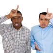 Closeup portrait of funny men displaying loser signs on their head and looking at you with disgust at camera gesture — Стоковое фото