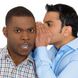 Stock Photo: Closeup portrait of guy whispering into man's ear telling him something secret and disturbing