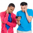 Closeup portrait of two young men looking upset while watching something on their cell phone, a text message, sms or email — Stock Photo #37755605