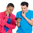 Closeup portrait of two young men looking upset while watching something on their cell phone, a text message, sms or email — Stock Photo