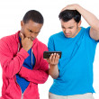 Closeup portrait of two young men looking upset while watching something on their cell phone, a text message, sms or email — Stock Photo #37755611