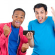Closeup portrait of two men looking shocked with opened mouth on a cell phone watching a football game or reading an sms, e-mail viewing latest news — Stock Photo