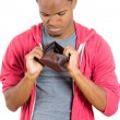 Closeup portrait of stressed, upset, sad, unhappy young man standing with, looking into empty wallet — Stock Photo #37756043