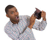 Closeup portrait of stressed, upset, sad, unhappy young man standing with, showing you empty wallet — Stock Photo