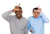 Closeup portrait of funny men displaying loser signs on their head and looking at you with disgust at camera gesture — Stock Photo