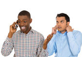 Closeup portrait of loud obnoxious rude guy talking loudly on cell phone, man next to him is pissed off and closes ears — Stock Photo