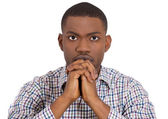 Closeup portrait of young man with open eyes praying hoping for the best asking for forgiveness or miracle looking at camera — Stock Photo