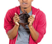 Closeup portrait of stressed, upset, sad, unhappy young man standing with, looking into empty wallet — Stock Photo