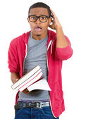 Closeup of a young handsome man, wearing big glasses, holding books, anxious in anticipation of finals, exam test — Stock fotografie
