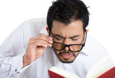 Nerdy guy trying to read book — Stock Photo