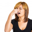 Woman with disgust on her face who covers pinches her nose — Stock Photo