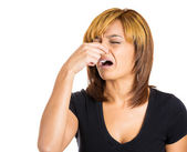 Woman with disgust on her face who covers pinches her nose — Foto de Stock