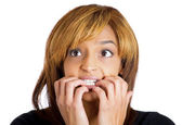 Unhappy woman wide open eyes biting her nails — Stock Photo