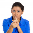 Woman placing finger on lips, pointing at you as if to say, shhhhh, quiet — Stock Photo #39733249