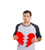 Confused man holding broken heart — Stock Photo
