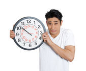 Man stressed holding clock — Photo