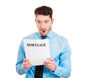 Man looking disgusted at his mortgage statement — Stockfoto
