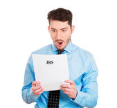 Man looking disgusted at his IRS statement — Stock Photo