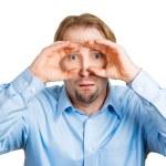 Curious man peeking through his fingers — Stock Photo