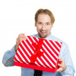 Young man about to open unwrap red gift box — Stock Photo #43714681