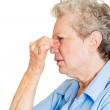 Senior mature woman pressing nose with fingers — Stock Photo